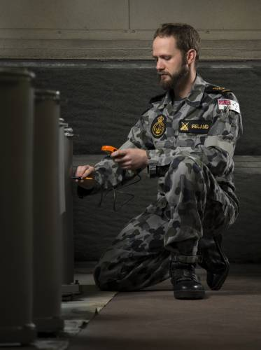 Petty Officer Bosun Luke Ireland conducts paint thickest checks on recently painted chaff launcher tubes at the HMAS Stirling Fleet Support Unit's Corrosion Control section.